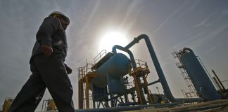 Man walking past oil field equipment and structures (© Haidar Mohammed Ali/AFP/Getty Images)