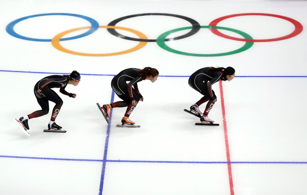 Tres patinadoras con el logo olímpico (© Ronald Martinez/Getty Images)