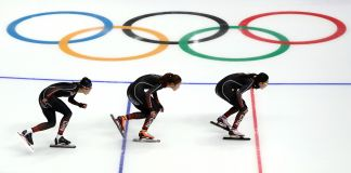 Three speedskaters skating by Olympic logo (© Ronald Martinez/Getty Images)
