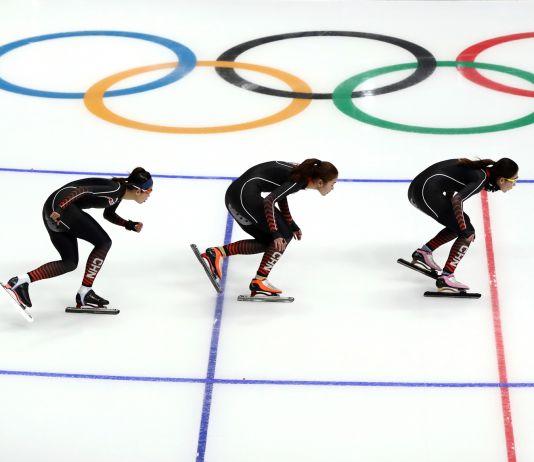 Três patinadoras de velocidade junto a logotipo olímpico (© Ronald Martinez/Getty Images)