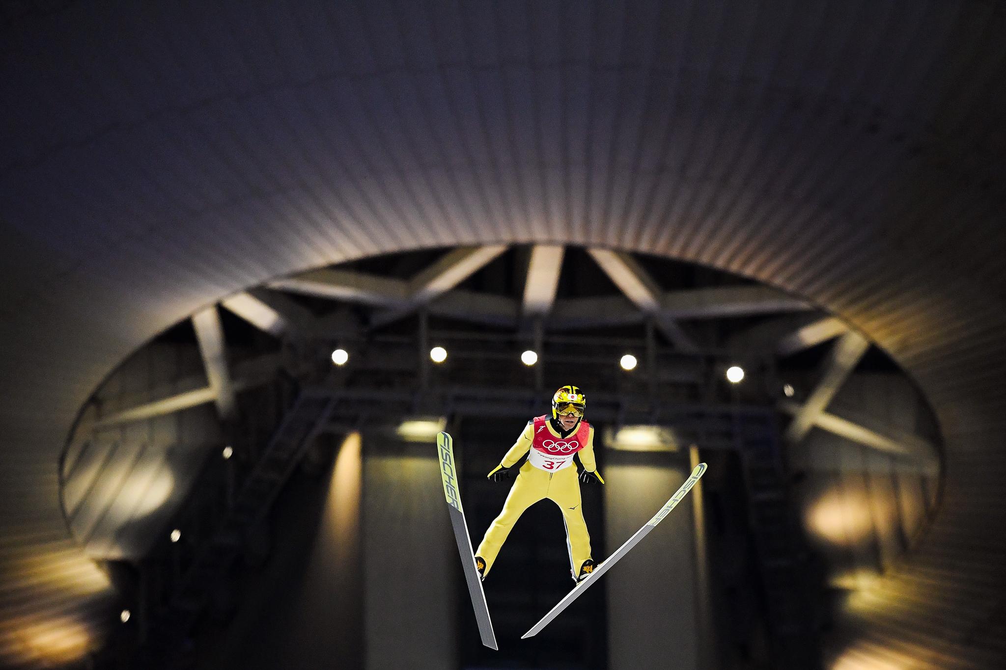 Atleta de salto de esqui em pleno ar. Ao fundo, uma arquitetura dramática. (© Quinn Rooney/Getty Images)