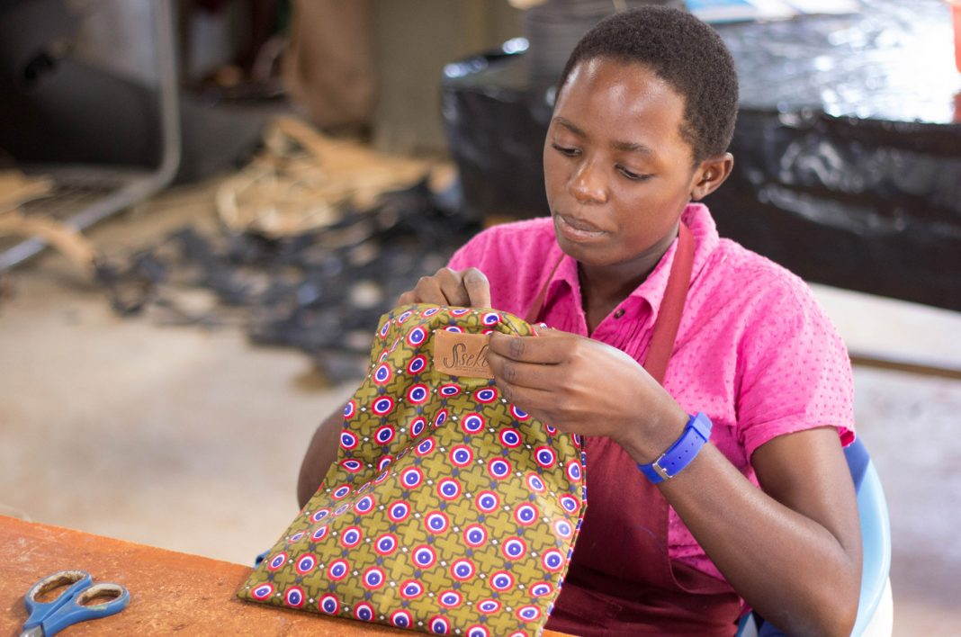 Woman sewing label into fabric bag (© Sseko Designs)