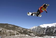Chloe Kim in air on snowboard, with blue sky and mountains in background (Sean M. Haffey/Getty Images)