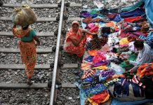 Woman with bundle on her head walking past people selling bright fabric along railroad (© Rupak De Chowdhuri/Reuters)