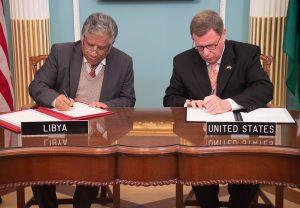 Dos hombres sentados firmando un documento (Depto. de Estado)