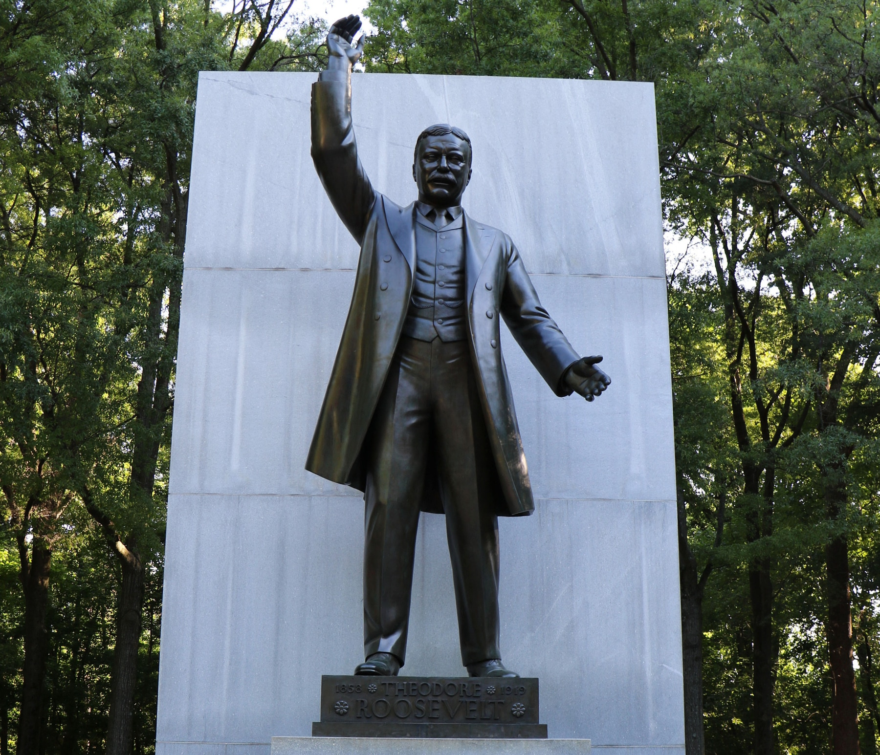 Bronze statue of Theodore Roosevelt with raised hand in front of large stone slab (National Park Service)