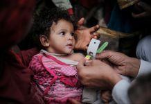 Une petite fille en train de se faire examiner pour déterminer son niveau de malnutrition, un mètre ruban autour du bras (© UNICEF/Almang)