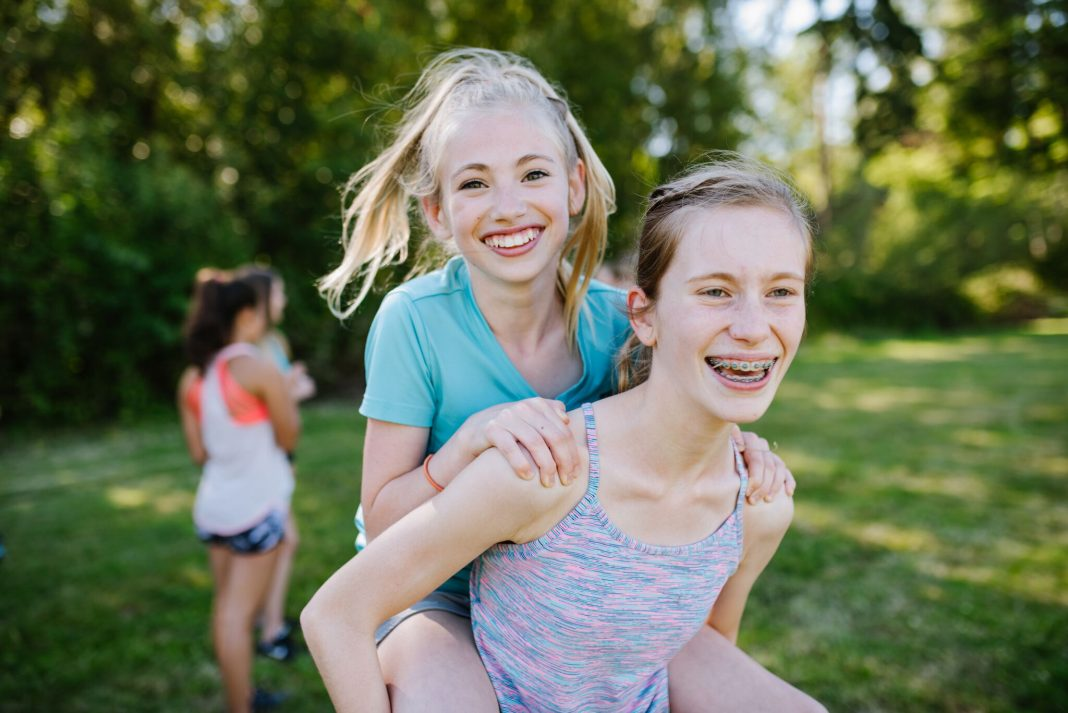 Girl riding on another girl's back (© Jane G. Photography)