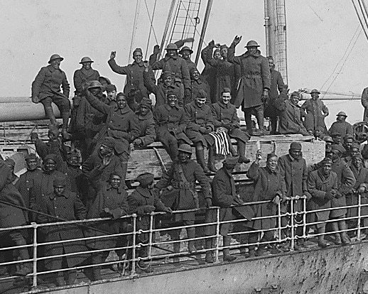 Soldiers lining boat deck and cheering (National Archives)