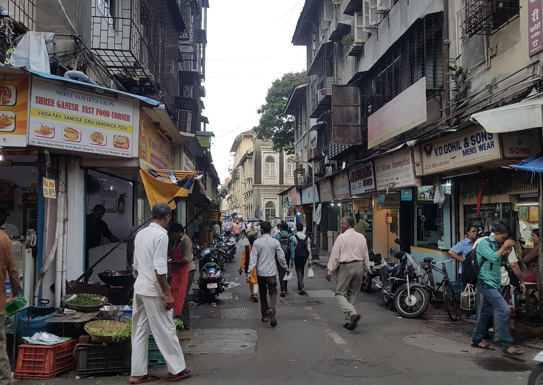 Pessoas caminhando por uma rua repleta de pontos comerciais em Mumbai, Índia (Shutterstock)