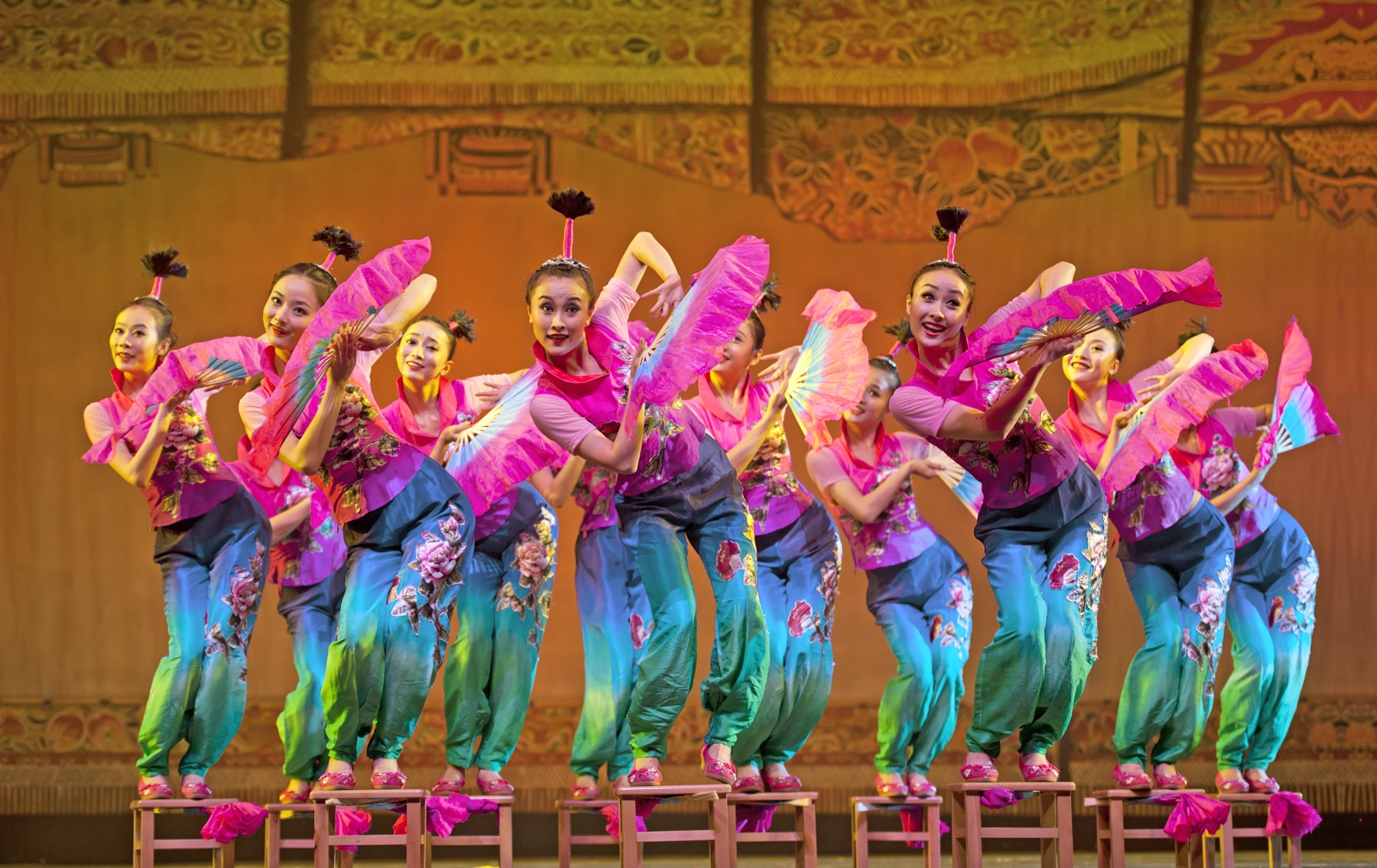 Young Chinese women in colorful garb dancing onstage (Shutterstock)