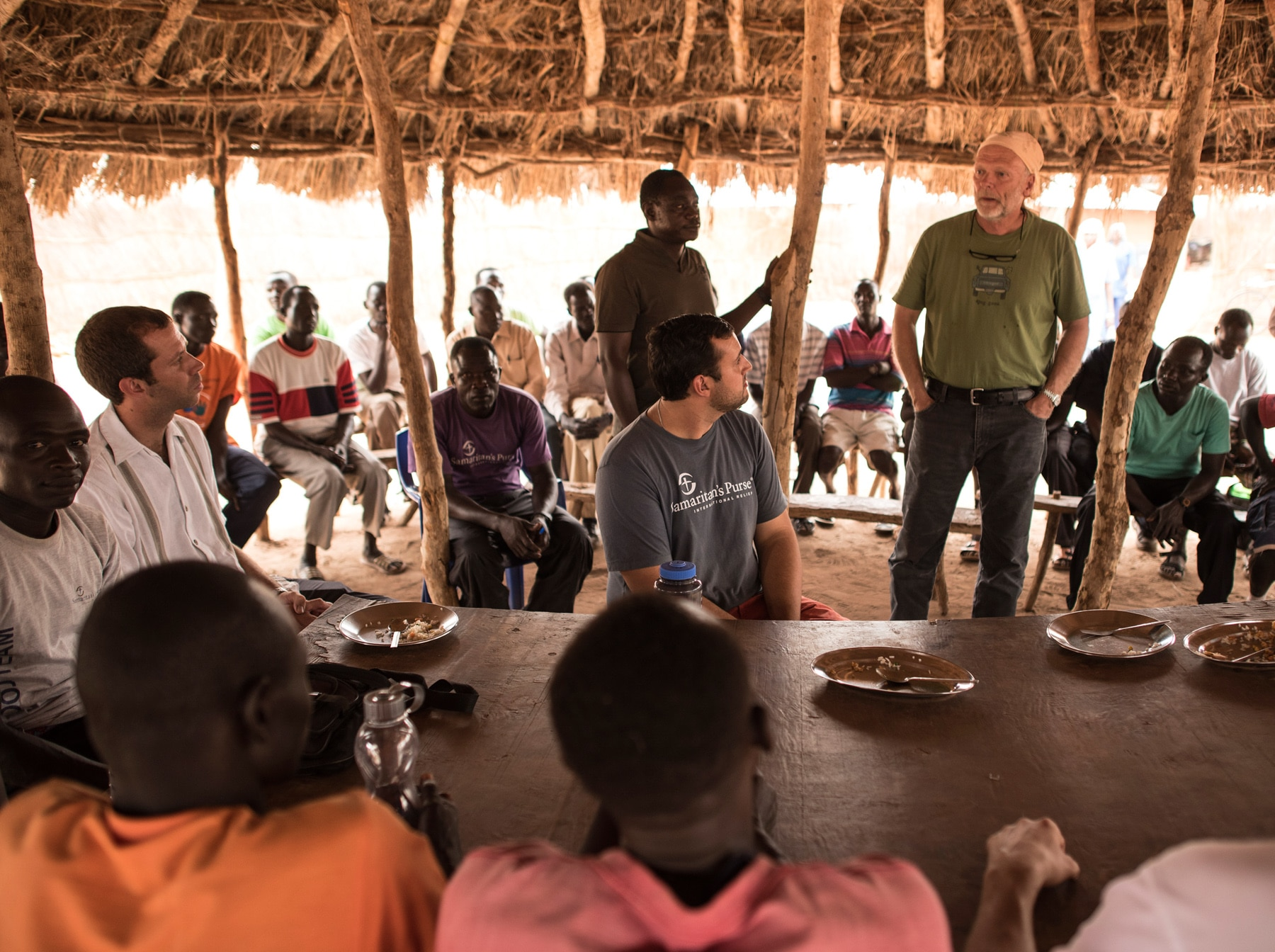 Ken Isaacs standing under hut, with men standing and seated around him (Samaritan's Purse)