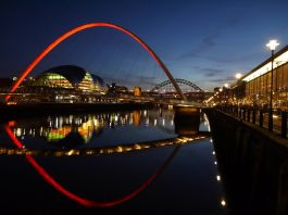 Bridge lit in red reflected in river at night (Stop TB Partnership)