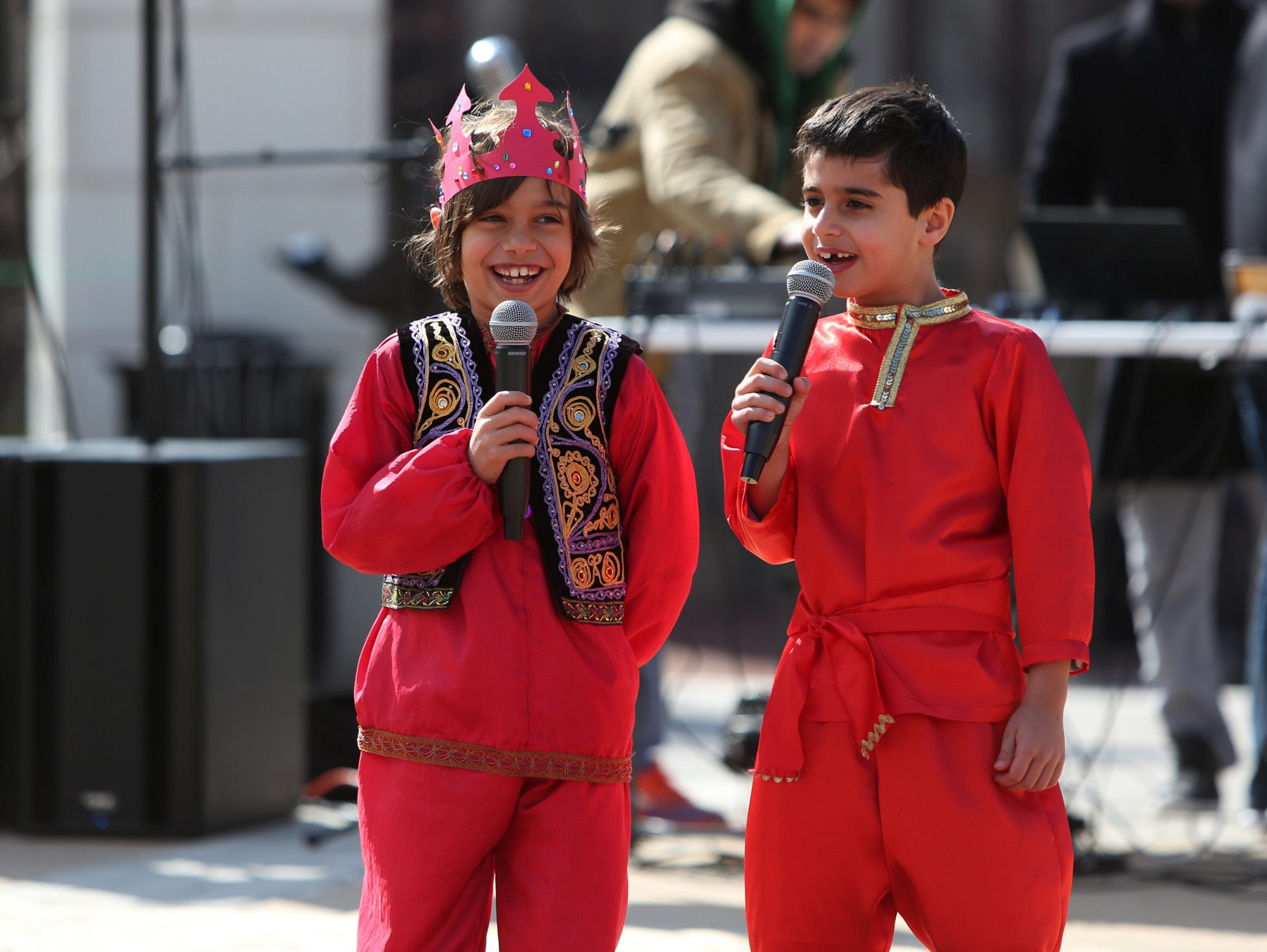 Two boys in red costumes speaking into microphones on a stage (© Ali Khaligh)