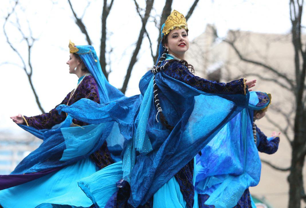 Mulheres usando vestidos azuis dançam no palco (© Ali Khaligh)