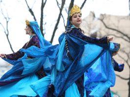 Women in blue dresses dancing onstage (© Ali Khaligh)
