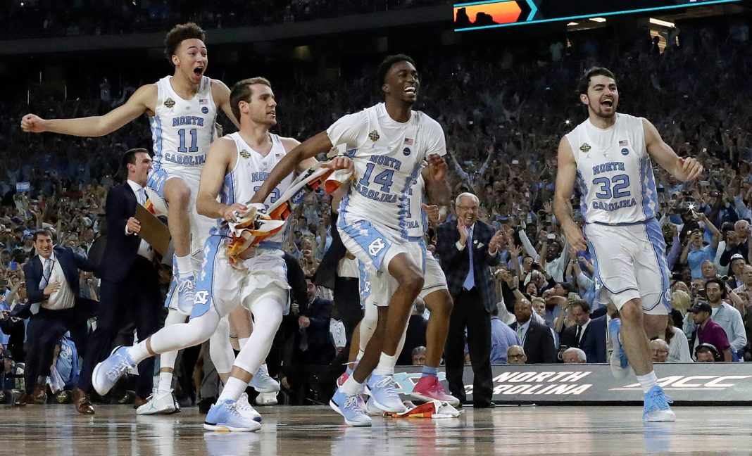 Basketball players jumping on court in celebration (© David J. Phillip/AP Images)
