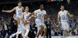 Des joueurs et des hommes en tenue de ville se précipitant sur un terrain de basket, l'air très heureux (© David J. Phillip/AP Images)
