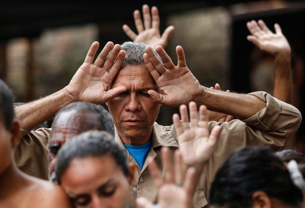 Des gens au milieu d'une foule, les mains levées vers le ciel (© Fernando Vergara/AP Images)