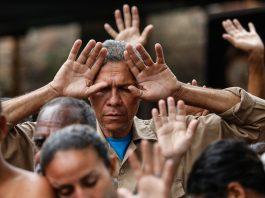 People in crowd holding hands in air (© Fernando Vergara/AP Images)