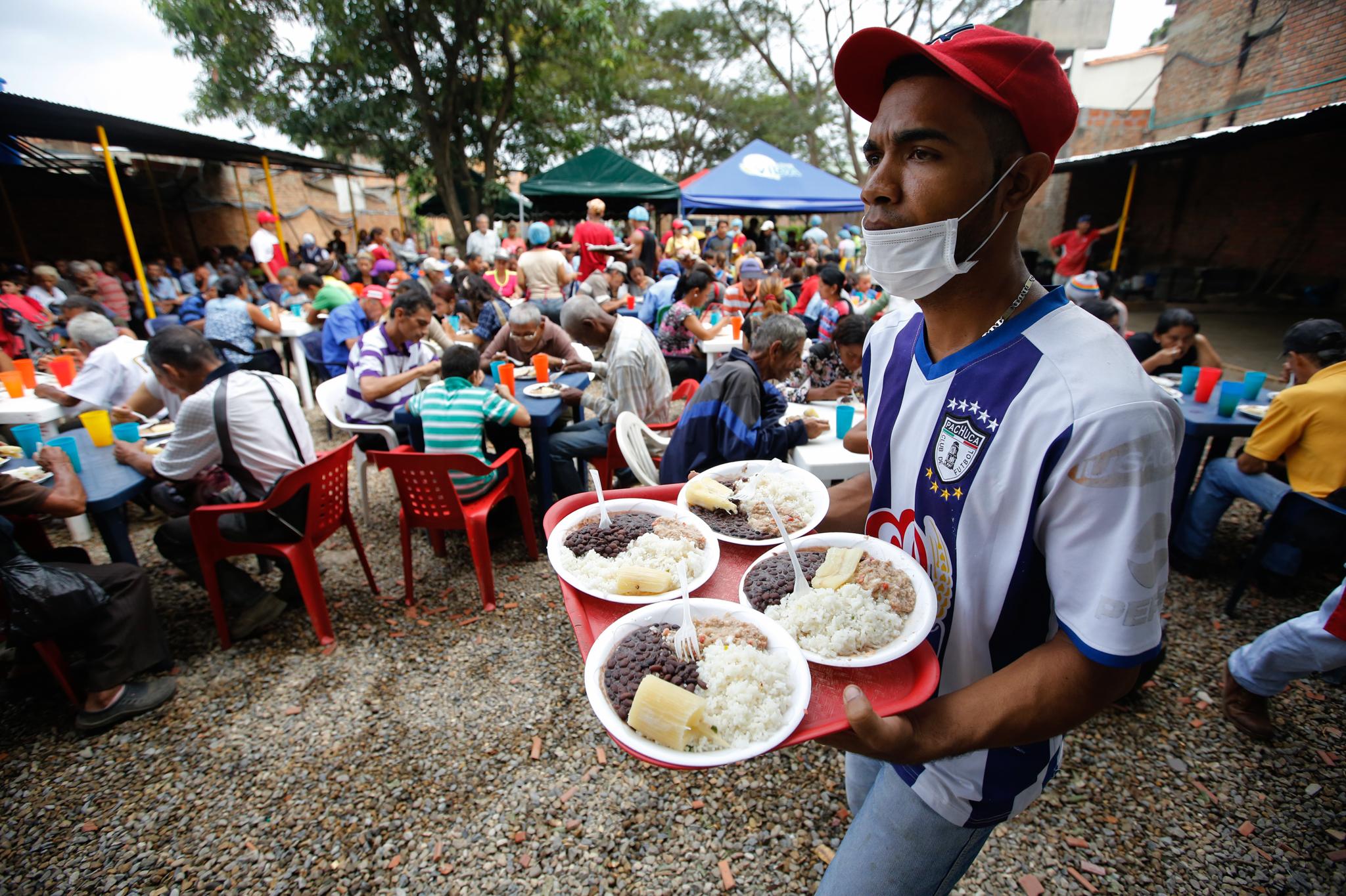 Un homme portant un plateau avec quatre assiettes ; autour de lui, un grand nombre de gens en train de manger à des tables en plein air (© Fernando Vergara/AP Images)