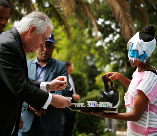 Secretary Tillerson receiving coffee from an Ethiopian woman (© Jonathan Ernst/AP Images)