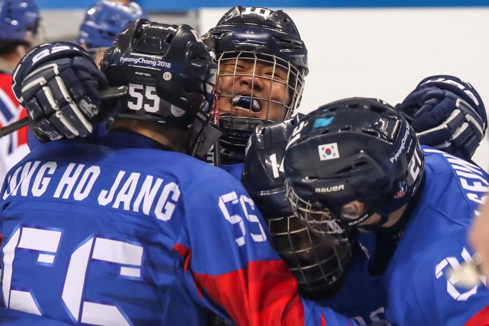 Man smiling in huddle of players (© Ng Han Guan/AP Images)