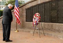 Rex Tillerson, la tête baissée devant une gerbe déposée au pied d'un mur (© Jonathan Ernst/AP)