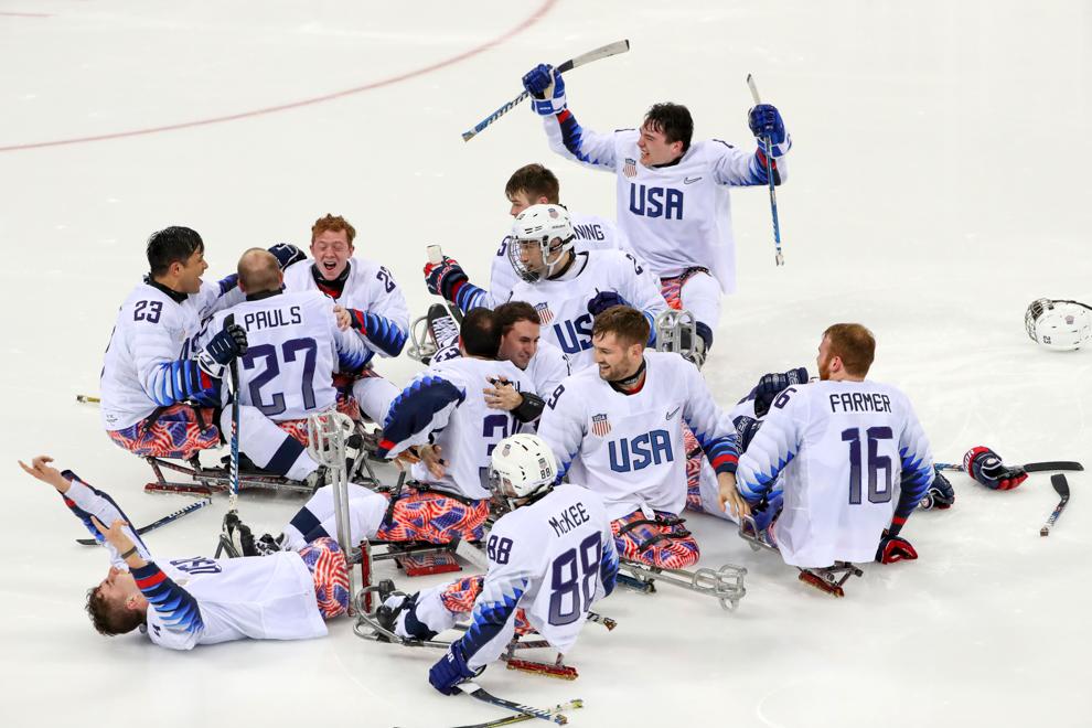 Hockey team celebrating on ice (© Ng Han Guan/AP Images)