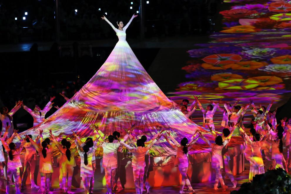 Woman raised high above fellow performers (© Ng Han Guan/AP Images)