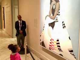Young girl looking at large painting hanging on wall (© Ben Hines)
