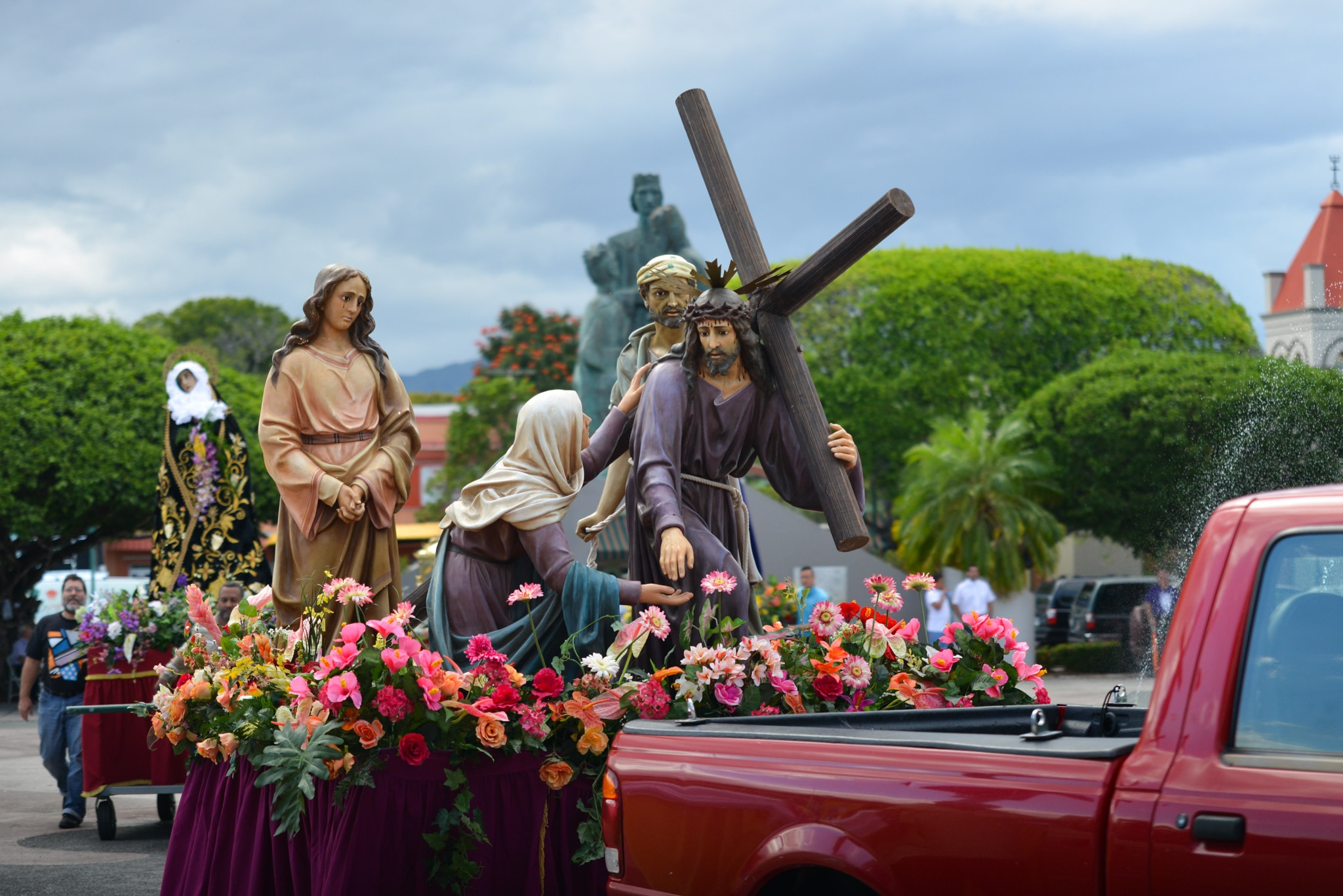Statues and flowers on float being pulled by truck (© Marina Movschowitz/Alamy)