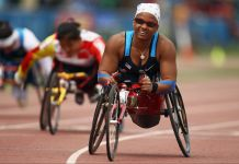 Smiling woman racing in lightweight wheelchair on a track (© Hannah Peters/Getty Images)