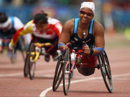 Une femme souriante participant à une course en fauteuil roulant léger sur une piste (© Hannah Peters/Getty Images)