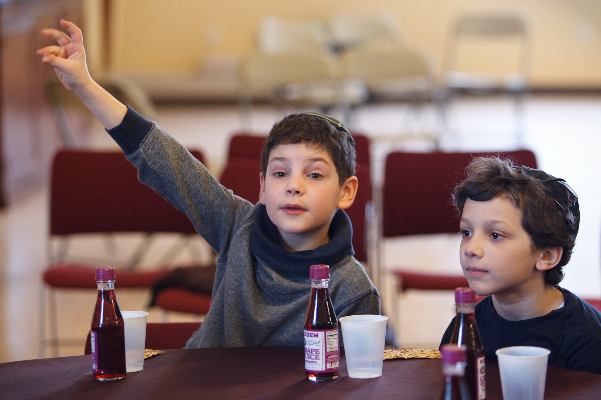 Two boys wearing yarmulkes sitting at table, one raising his hand (© Dina Rudick/The Boston Globe/Getty Images)