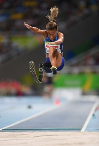 Woman with prosthetic leg jumping in a track event (© Atsushi Tomura/Getty Images)