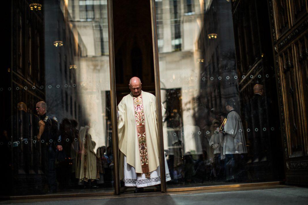 Homem vestindo roupas religiosas junto às portas de uma igreja (© Eduardo Munoz Alvarez/VIEWpress/Getty Images)