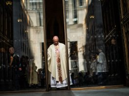 Man wearing religious robes at doors of church (© Eduardo Munoz Alvarez/VIEWpress/Getty Images)