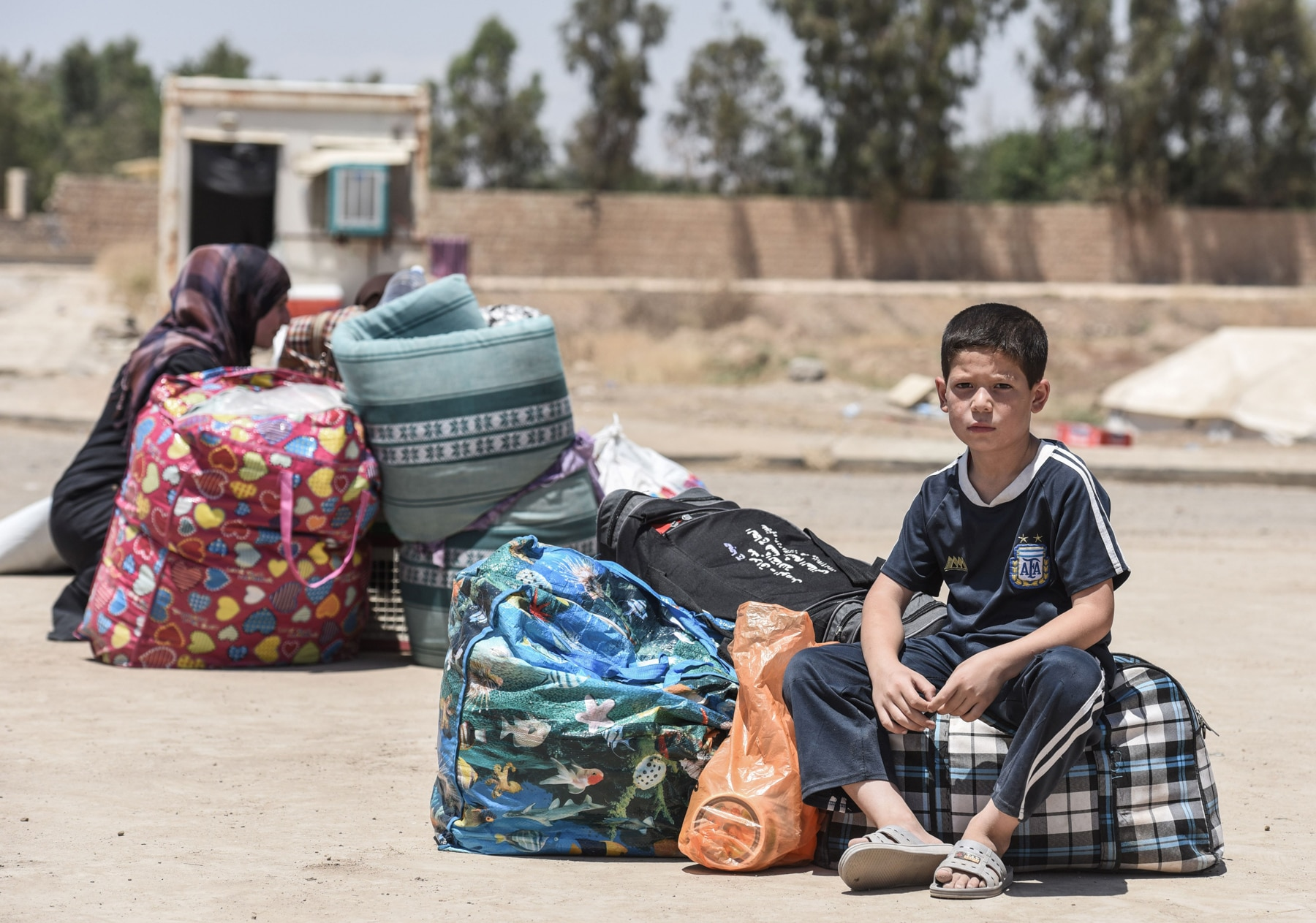 A boy sitting on his belongings in the street (© Mohamed el-Shahed/AFP/Getty Images)