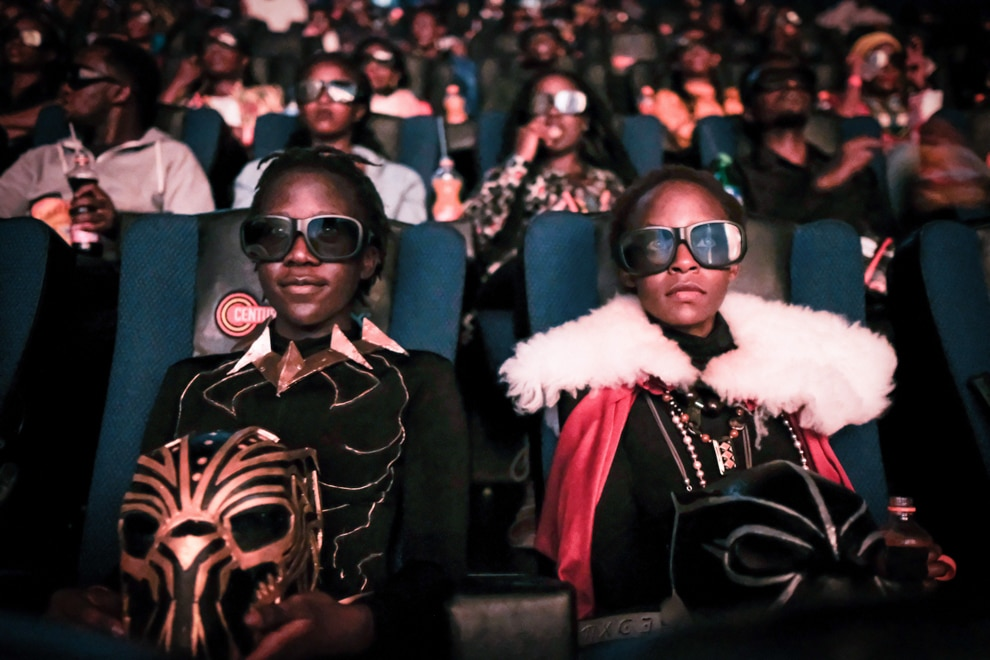 Picture of two youngsters dressed in costume sitting in movie theater (© Yasuyoshi Chiba/AFP/Getty Images)