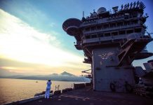Person standing on deck of aircraft carrier (© Linh Pham/AFP/Getty Images)