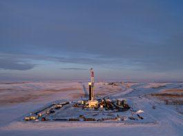 Plataforma on-shore de perfuração de petróleo em paisagem coberta de neve (© Daniel Acker/Bloomberg/Getty Images)