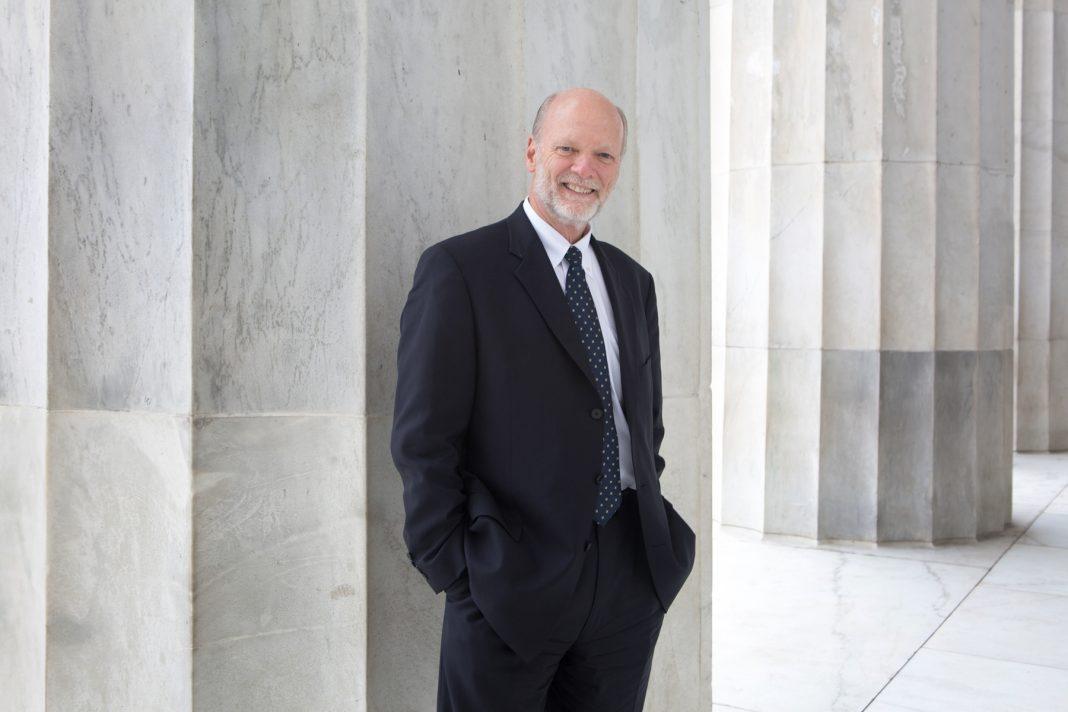 Ken Isaacs de pé na frente de pilar branco (D.A. Peterson/Departamento de Estado)