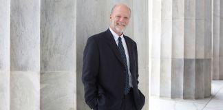 Ken Isaacs standing in front of white pillar (D.A. Peterson/State Dept.)