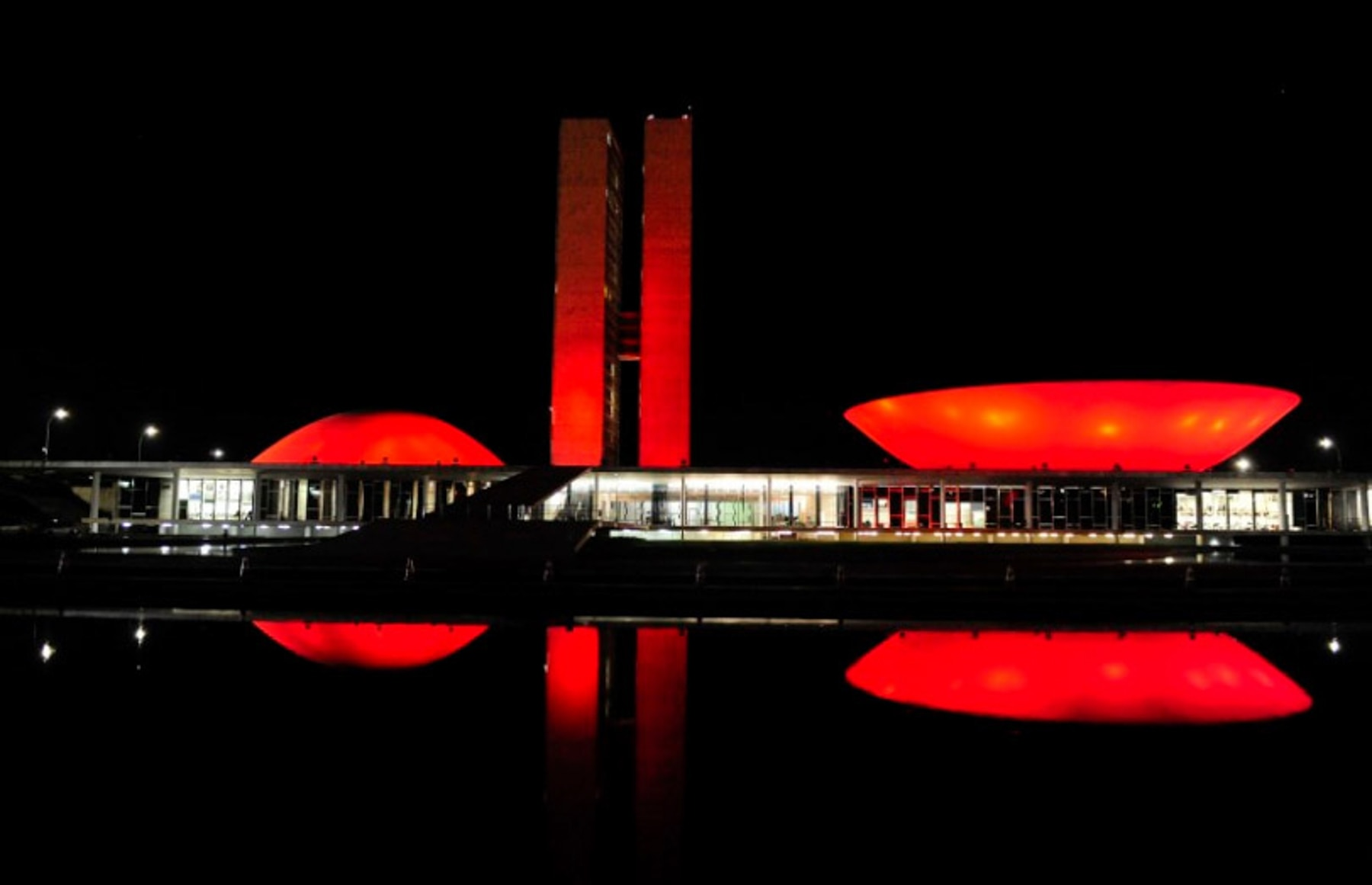 Building shining red and reflected in water at night (Stop TB Partnership)