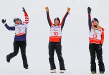 Three women in cold-weather clothes cheering (© Paul Hanna/Reuters)