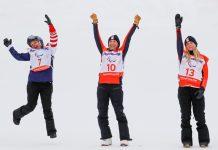 Tres mujeres con ropa abrigada animando a los atletas (© Paul Hanna/Reuters)