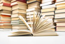 Open book and stacks of books (© Shutterstock)