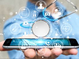 Hand holding cellphone with medical icons floating above it (Shutterstock)