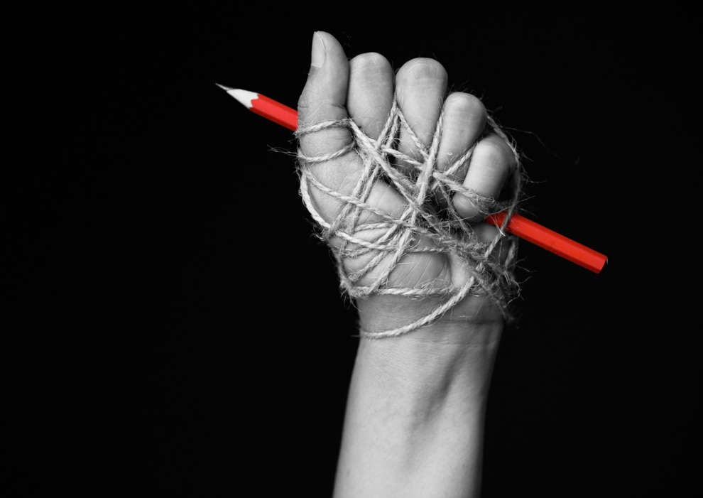 Rope wrapped around fist holding red pencil (© Shutterstock)